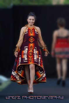 Dineh-Couture by Michelle Silver(a Phoenix- based Navajo Designer). Her designs arise from a unique enthusiasm from Pendleton blankets. Drawing inspiration from the Navajo tradition and modern fashion. Her label, Dineh Couture, reflects elegance, tradition, and contemporary design. Her line emphasizes the female figure, making the classic Pendleton wearable as haute couture. Michelle was a feature designer for The Woman of the Navajo Calendar in 2009 (winner of the North American Indigenous…