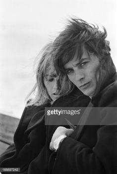 Rendezvous With Alain Delon And Nathalie. Attitude de Nathalie DELON regardant un oiseau caché sous le caban de son mari Alain DELON sur la dune du PYLA, tous deux cheveux au vent..