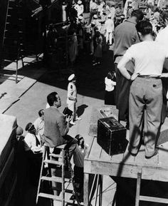 Behind-the-scenes, on the set of CASABLANCA (1942)     Humphrey Bogart takes a moment to shoot home movies of the production.  He is pictured above, on the ladder, with his movie camera.