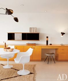 the kitchen of the renovated Singleton House by Richard Neutra features a Saarinen Tulip table, chairs by Knoll and built-in cabinets by Neutra; the hanging cabinet and stool are by Jean Prouvé