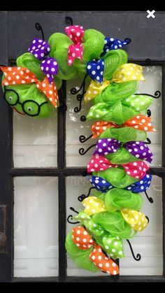 Back to school wreath. Bookworm wreath. Caterpillar wreath. Back to school time is right around the corner and this bookworm wreath is the perfect back to school wreath, back to school decoration, gift for teacher, etc.... This cute bookworm measures 35 long X 18 wide. Made with lime green deco mesh. Decorated with multiple color polka dot wired ribbon, cute little black glasses and legs made out of black fuzzy sticks, and a red smile on its face. Available in most colors to match school…