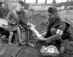 A Canadian medic lending his medical assistance and gear to a wounded child.