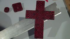 Polymer cross with a red and black pattern