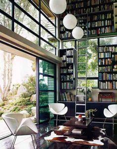 Großes, offenes Wohnzimmer mit Kuhfell, riesigem schwarzem Buchregal bis unter die Decke und Leiter