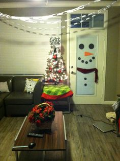 Easy Christmas DIY. One of my favorite decorations is the snowman on the door. I used an old scarf hung by command strip hooks, and paper cut-outs. I also made paper chains hung from the ceiling.
