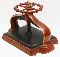"""ANTIQUE RED AND GOLD BOOK PRESS  Antique book press. Has a red finish with gold trim design. Measures approx. 12"""" height x 19 1/2"""" length x 12"""" depth"""