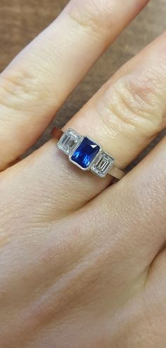 The blue sapphire engagement ring has a natural emerald cut sapphire nestled between two emerald diamonds. The setting style is rubover which securely holds the gemstones from all sides. The Art Deco influence ring has a millegrain edge in keeping with the vintage look. #LondonVictorianRing #BlueSapphireRing #SapphireRing #SapphireEngagementRing #BlueGemstone #NaturalSapphire Three Stone Engagement Rings, Three Stone Rings, Designer Engagement Rings, Blue Sapphire Rings, Emerald Cut Diamonds, Diamond Cuts, Natural Sapphire, Natural Emerald, Blue Gemstones