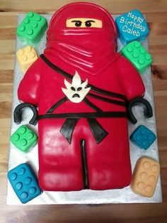 Lego Kai Ninjago cake - My first carved cake with home made marshmallow fondant. I was worried about covering the carved cake with fondant. had only covered round cakes but it turned out pretty good. better than the picture of the cake my friend had given me. he has legos around him too made of cake. ( would have done them in rice krispy to get the squared look but she wanted them in cake.