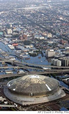 2005 New Orleans a would be safe place for those displaced by the storm...super dome battered roof  & surrounding area under water-  hurricane Katrina- everyone who came here had to be evacuated