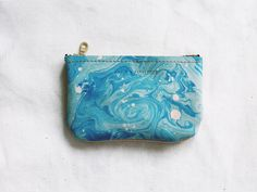 """Tonala is an artisan community in Guadalajara, Mexico's second largest city, known for it's diverse range of handmade wares. This series of simple soft leather goods is inspired from my time wandering Tonala's streets, learning from it's local makers.The Pequena size is perfect as a small wallet or zipper pouch.~ hand marbled leather in bright blue~ thick natural vegetable tanned leather on back side - this leather darkens with light and wear.~ gold YKK 5.5"""" zipper..."""