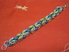 Elegante bracciale fatto a mano con anelli in alluminio di colore turchese, blu elettrico ed oro, chiusura argentata. Diametro anelli 1,5 - Lunghezza bracciale cm 27