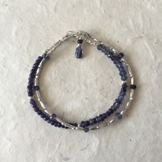 Iolite Karen Hill Tribe Thai silver beaded bracelet with dangle Bracelet measures 7 inches, or custom size ♥♥♥♥♥♥♥♥ Iolite metaphysical properties: Power, inner strength, leadership, self-confidence ♥♥♥♥♥♥♥♥ ***Please note*** Gemstones are works of nature, therefore, can have differences in color and may have inclusions. Because of this, your piece may vary slightly from what is pictured. Thai Silver or Karen Hill Tribe Silver are all completely handmade in northern Thailand. Each piece ...