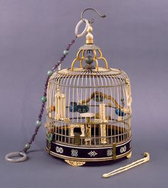 Hanging type, circular dome shape with tall finial, silver hanger. Components: 1 cage 1 beaded ring 4 water bowls 1 cylindrical feeder 1 mini birdcage 1 coral feeder 2 hanging rings 2 perches 1 ivory ornament with metal bugs 2 jade clips 3 ivory clips 1 ivory stick