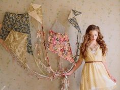 Make your own kites, tail with pretty embellishments and hang from the wall for a unique interactive photo backdrop.  Link is how to make 9 DIY Kites - from All Women Stalk
