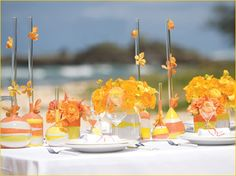 """Clear vases are filled with orange, yellow and white sand to create a playful & artistic """"wave"""" pattern."""