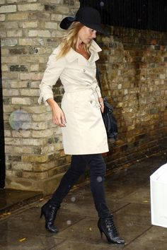 Kate Moss in black skinny jeans and light-colored trench, worn with black accessories.