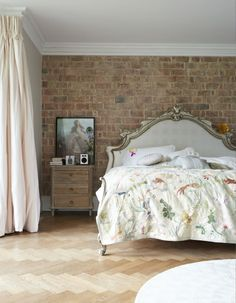 Exposed brick wall, parquet flooring and a Lulu Guinness bedspread