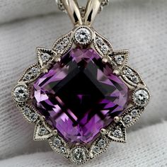 The amethyst is just shy of 12 carats and is set with surrounding diamond detail in 18k unplated white gold. Lovely!