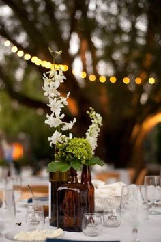 Love the way the old liquor bottles work in this centerpiece ... Perfect for a 1920s speakeasy theme.