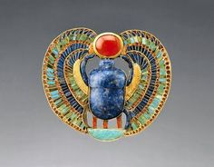 This piece of Egyptian jewelry is from the tomb of Tut-ankh-amun (Tutankhamun).    A scarab of lapis lazuli with falcon wings, supporting a red disk of the new-born sun.