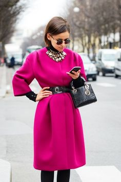 pink coat with a black accent belt, small bag, and a large statement necklace