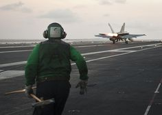 PACIFIC OCEAN (April 23, 2013) A Sailor prepares to guide arresting gear on the flight deck of the aircraft carrier USS Nimitz (CVN 68). Nimitz and Carrier Air Wing 11 recently left San Diego for a Western Pacific deployment. (U.S. Navy photo by Mass Communication Specialist 3rd Class Raul Moreno Jr./Released)