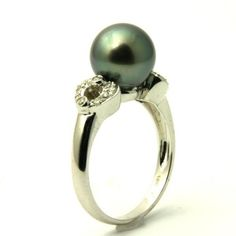 Cultured Tahitian Black Pearl & Diamond Engagement Ring - Heart shapes come on both sides of this incredible Cultured Tahitian Black Pearl & Diamond Engagement Ring stamped in an 18k White Gold featuring a Light Mystic Topaz colored Pearl set on the top of the ring along with White accent stones on the heart shape portion of the shank. This Black Pearl ring is 9.6mm in diameter & the total gem weight is equal to .18 carats. #unusualengagementrings