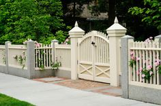 residential house with fencing and gate made from wood, brick, and granite, pink rose bushes come through picket posts