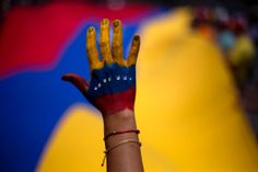 A woman with her hand painted with the colors of the Venezuelan flag attends a rally in support of opposition leader Leopoldo Lopez, in Caracas, Venezuela on June 8, 2014. Anti-government activists massed to voice support for hard-line opposition leader Leopoldo Lopez, who has been held in a military prison since being arrested in February on charges of fomenting violence as a result of the initial protests. A judge ordered last week that Lopez proceed to trial.