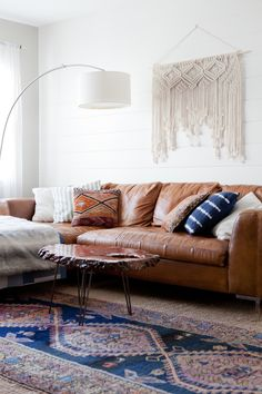 Dark leather couch, macrame wall hanging, white oversized lamp, Persian blue and purple boho rug, wood coffee table