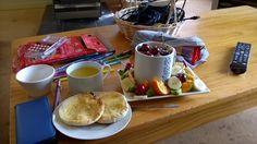 Muesli and custard trifle topped with cherries, surrounded by banana, kiwifruit, orange and more cherries. Plus an English muffin with margarine and orange juice.
