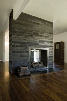 Great combo of rustic grey reclaimed wood and warm distressed wood floors..love double sided fireplaces too.
