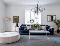 Rosa sittpuff och rosa kuddar. Flos takkrona och blå soffa i vardagsrummet.