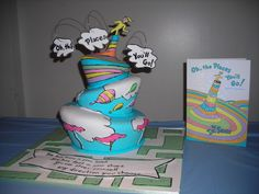 Oh, The Places Youll Go - Baby Shower Cake inspired by Dr. Seusss classic book! Topsy Turvy cake with handpainted elements from the book, sculpted funnel on top, wired clouds with the title, and resting on a handpainted maze with Mom-To-Bes favorite book quote.