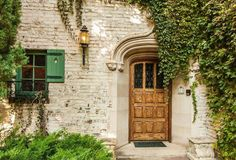 Tucked away on a lush two-acre property, this home's charming front door is par. - Tucked away on a lush two-acre property, this home's charming front door is partially draped in - Patio Doors, Entry Doors, Front Door Lighting, Front Door Makeover, English Country Decor, Wooden Front Doors, Front Door Colors, Patio Seating, Windows And Doors