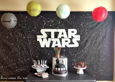 For the dessert table backdrop, I used a black plastic tablecloth and splattered it with white paint to look like the galaxy. I used my Silhouette to cut out the Star Wars logo on white vinyl. For the planets and Death Star hanging above the table, I used some paper lanterns that I had on hand and spray painted them.