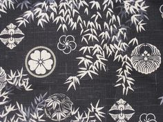 Japanese Cotton Kimono Fabric - Bamboo Crests in Blue and Black  Detail of a beautiful bolt of vintage Japanese cotton fabric used to make everyday kimonos. The pattern features crests of Samurai (military noble families of pre-industrial Japan) houses, woven in white amid bamboo leaves against a black and blue background.