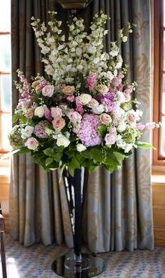 """LIKE THE COLORS ONLY Wedding Flowers """"Fabulously grand floor standing vase display for your wedding ceremony room. A tall display makes a dramatic impact with tall elegant ivory delphiniums, pale pink larkspur and scented stocks, amongst a dreamy mass of roses including Avalanche roses, Sweet Avalanche roses, Amnesia roses, unusual Vuvuzuela roses, blousy hydrangeas and dainty lisianthus. Ask your wedding florist about vase hire. """""""