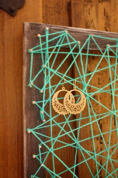 Wood Frame Earring Holder with Geometric Shaped Yarn á la String Art, very interesting! Though only for hanging earring, put on a little box for studs?
