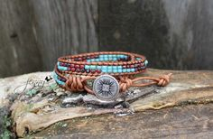 This leather beaded wrap features beads in red and blue. They were handwoven between 2 rows of natural brown leather. Fastens easily with a antique silver button.    So easy to wear, simply wrap around your wrist 2 times and fasten the button for a great casual look. Looks awesome with your favorite t-shirts, jeans and boots.    This wrap offers a two loop fitting. It measures 14 inches and 15 inches. Please measure your wrist carefully.    This bracelet was handmade by me. I make one of…