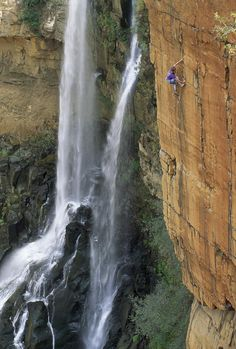 A Climber On A Cliff Next to a Waterfall
