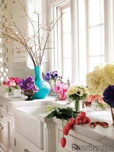 In a kitchen by Allison Caccoma, white cabinetry and marble countertops pop against the bright hues of the florals. Turquoise, pink, purple...they all come together for a lively look.