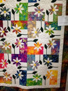 Appliqued flowers over a pieced block - beautiful! done with batiks