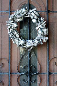DIY Skeleton Wreath...Materials needed: 5 miniature skeletons, 4 ft of pipe insulation (or a craft store wreath if you're fancy), duct tape, glue/glue gun, metallic spray paint (silver/black)