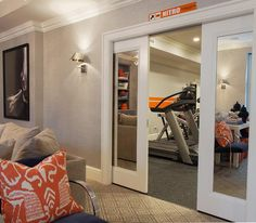 Mirrored pocket doors open to a basement workout room filled with exercise equipment.