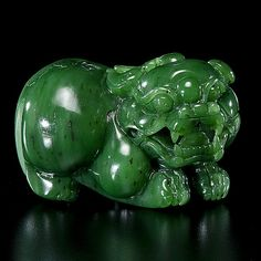 Chinese. A finely carved spinach jade recumbent foo dog; lg. 3 in.