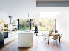 light filled kitchen in white with a large kitchen island and dinign area with mid century modern furniture