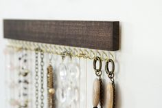 Stained and waxed wood necklace display with 23 hooks. 12 long by 2 tall (including hooks). Please choose the following options: gold/brass or silver/nickel hooks, and medium brown or deep brown stain. See the last photo for stain color samples.  Two sets of Command Velcro strips for hanging on the wall are included, one for each side of the display. Ive used mine quite a bit and found it to be very sturdy - and removable!  Please read 3Ms instructions on cleaning your walls and applying the…