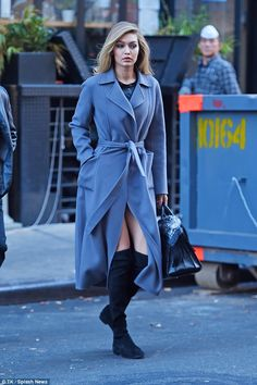 Accessorized:Under the long coat the Vogue favorite had on what appeared to be a black silk minidress. In the Los Angeles native's hand was a black alligator purse with a black bandanna tied on the handles