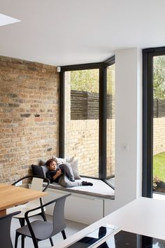 A glass roof above the stairs of this house enables daylight to filter down to the basement. A new bay window accommodating a window seat and a full-height folding glass door add to the natural lighting and provide a direct connection with the garden.